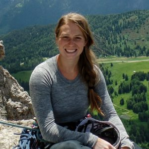 Graduate student Erin Murphy sitting on a rock with climbing gear